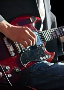 man playing loud music on guitar