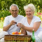 hearing elderly couple enjoying a picnic
