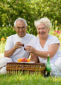 hearing elderly couple enjoying a picnic