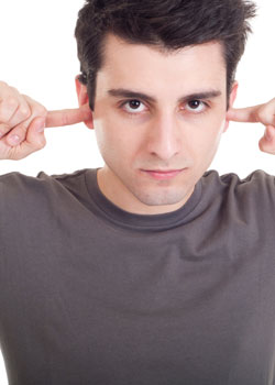 man trying to stop tinnitus by putting fingers in ears